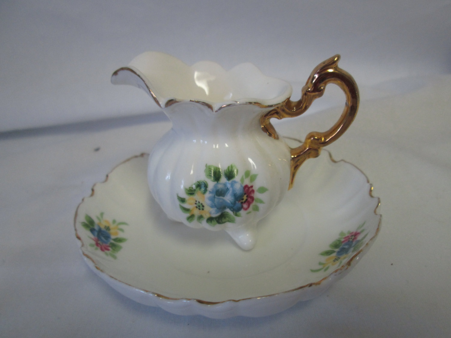 Beautiful Miniatrue pitcher and plate fine bone china floral trimmed in gold Mid century gold handle footed pitcher scalloped plate